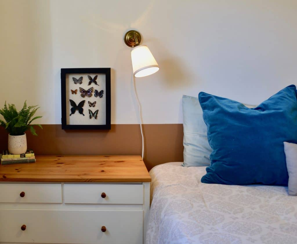 Guest bedroom bed and bedside table with waterproof mattress cover, ready for Airbnb rental of your home.