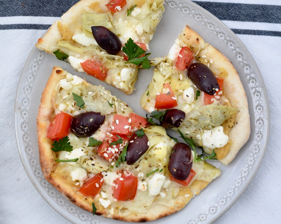 Easy Greek Pizza Recipe - Hummus, Feta, Tomatoes, Kalamata Olives, Artichoke Hearts, Fresh Oregano and Olive Oil.