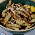 Lemon Parmesan Baked Potato Wedges | Skin-on Fries baked with lemon, butter and parmesan to create a completely delicious and surprising side dish.
