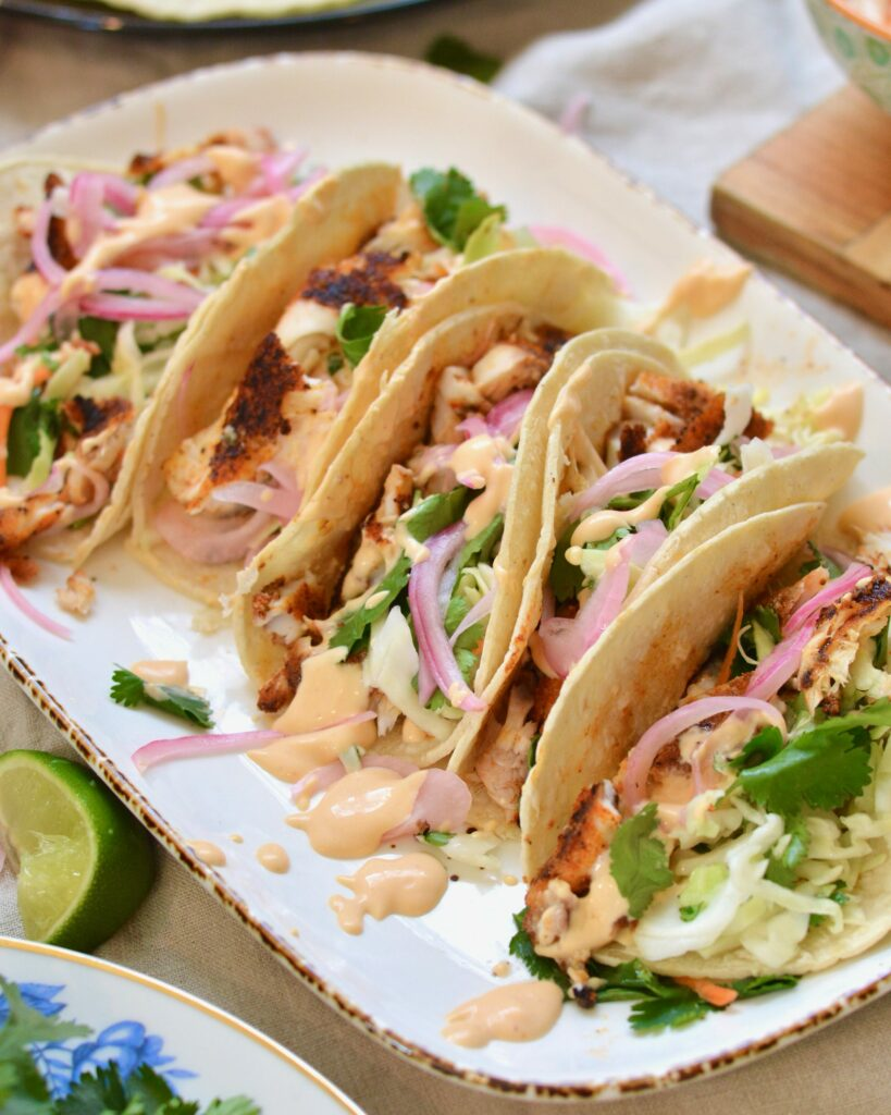 Super easy Blackened Fish Tacos with Tilapia, cilantro slaw and 2 ingredient sauce. Delicious taco night and summer meal.