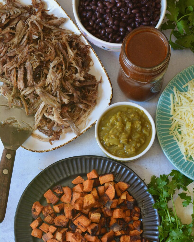 Delicious Make Ahead Enchiladas filled with Carnitas, Black Beans and Sweet Potatoes. Outstanding flavor combination of sweet, savory and spice. Simple homemade enchilada sauce recipe too!